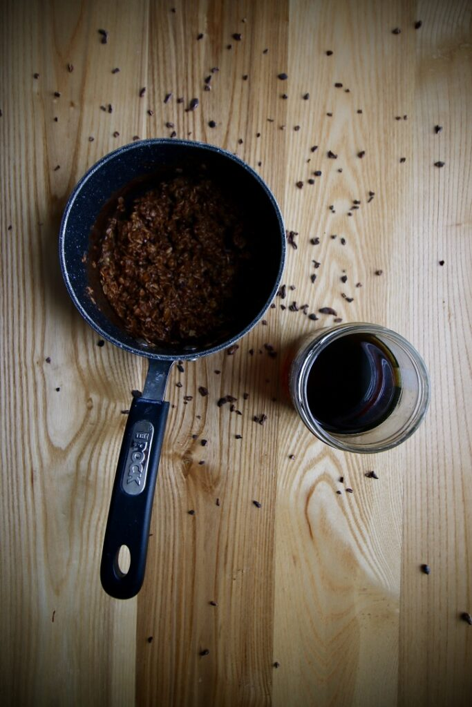 Vegan double chocolate oatmeal in The Rock small sauce pan with a jar of Canadian Maple Syrup